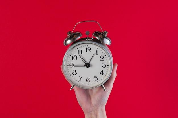 De vrouwelijke handen houden retro wekker op rode oppervlakte