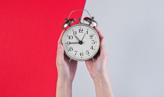 De vrouwelijke handen houden retro wekker op rood grijze oppervlakte