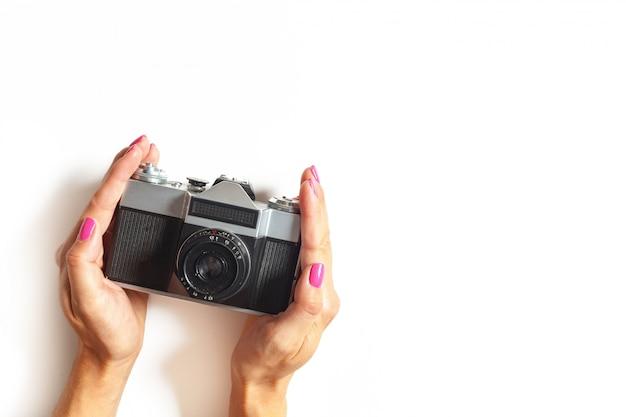De vrouwelijke handen houden uitstekende camera op wit