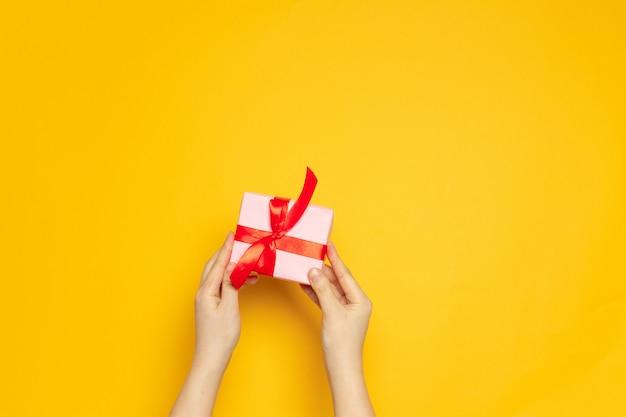 De vrouwelijke handen houden verrassingsdocument vakje met rood lint op geel
