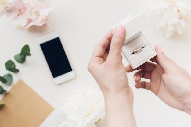 De vrouwelijke handen houden witte giftdoos van bloemen en telefoon. bovenaanzicht
