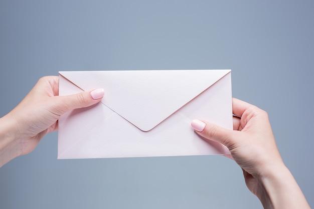 De vrouwelijke handen met de envelop tegen de grijze achtergrond