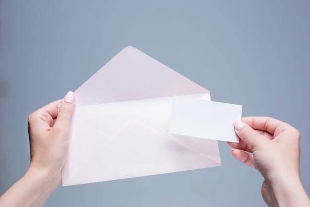 De vrouwelijke handen met envelop tegen de grijze ruimte