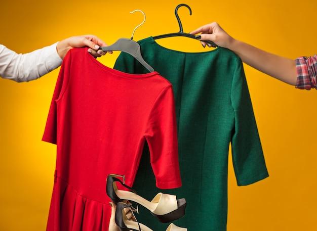 De vrouwelijke handen met nieuwe jurken op geel