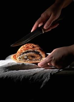 De vrouwelijke handen snijden gebakken broodje met papaverzaden op een houten plaat