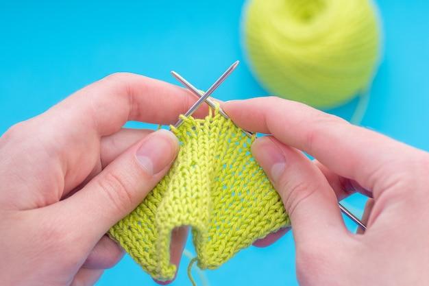 De vrouwelijke handen van de close-up breien op een klassiek patroon van de breinaald