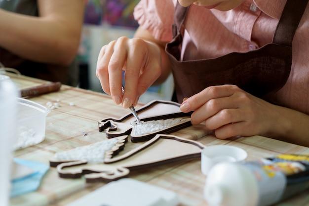 De vrouwelijke handenkunstenaar verzamelt mozaïek dicht omhoog