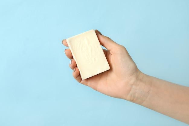 De vrouwelijke handgemaakte zeep van de handgreep op blauw