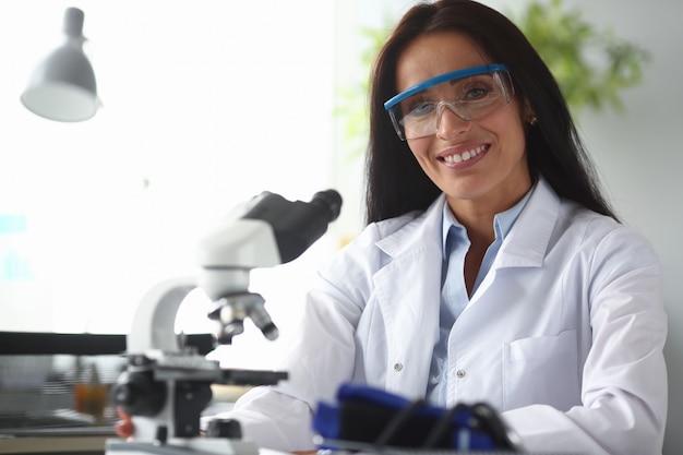 De vrouwelijke indische chemicus bekijkt camera tegen chemielaboratorium