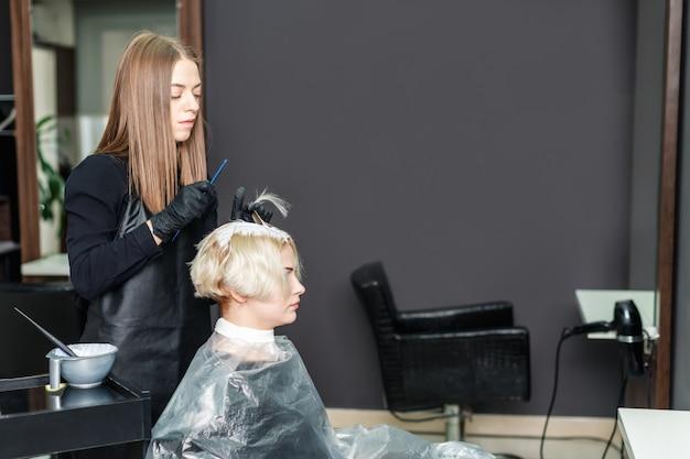 De vrouwelijke kapper brengt witte kleurstof op het vrouwenhaar aan.