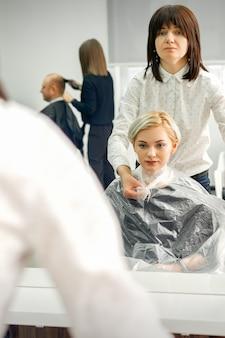De vrouwelijke kapper trekt een cape van transparant cellofaan naar de vrouwelijke klant in een schoonheidssalon