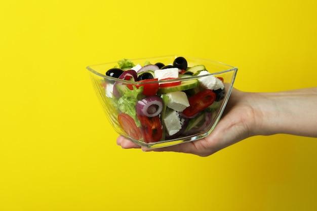 De vrouwelijke kom van de handgreep griekse salade op geel