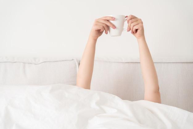 De vrouwelijke kop van de handholding van koffie van onder een deken in bed met exemplaarruimte