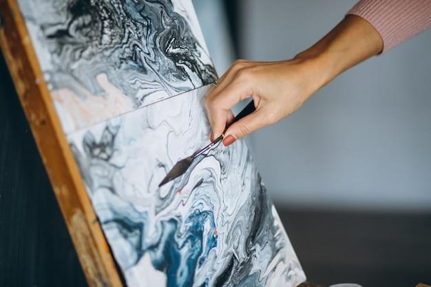 De vrouwelijke kunstenaar overhandigt dicht omhoog gebruikend paletmes