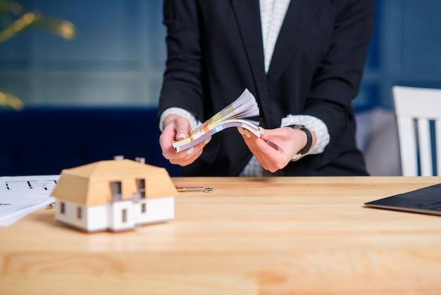 De vrouwelijke makelaar in onroerend goed overhandigt tellend geld na succesvolle overeenkomst voor het kopen van huis.