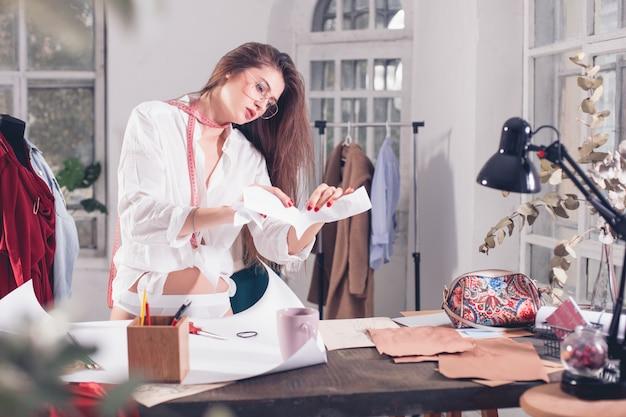 De vrouwelijke modeontwerper die in studiozitting op het bureau werkt