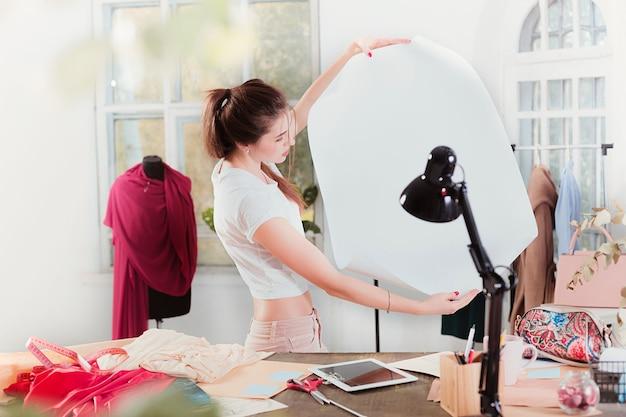 De vrouwelijke modeontwerper werkt in studio zittend op het bureau