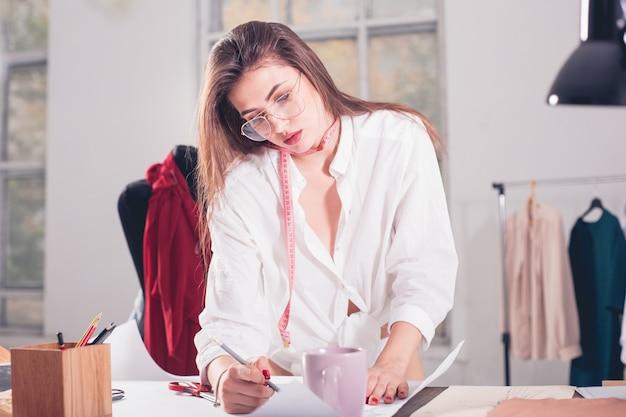 De vrouwelijke modeontwerper werkt zittend op het bureau
