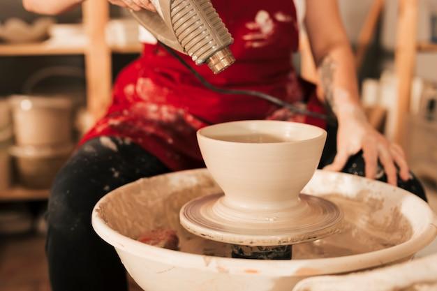 De vrouwelijke pottenbakker met een droogkap droogt een kleikom op het wiel van de pottenbakker