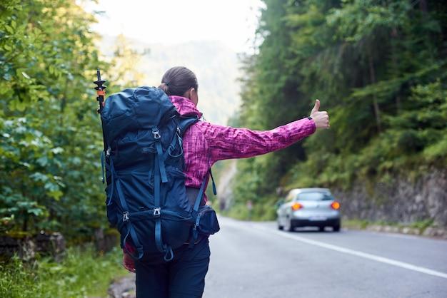 De vrouwelijke reiziger met rugzak haalt een auto op weg