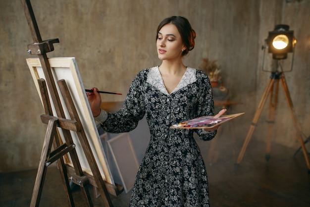 De vrouwelijke schilder met borstel en palet trekt in kunststudio