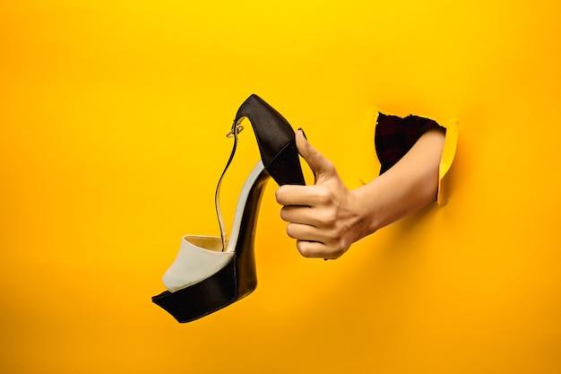 De vrouwelijke schoen bij de hand door een gescheurd geel papier