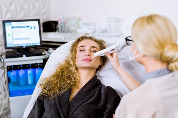 De vrouwelijke schoonheidsspecialist doet ultrasone gezichtsreiniging en pulstherapie voor de mooie zitting van de vrouwencliënt als voorzitter in een grijze laag in beauty spa kliniek