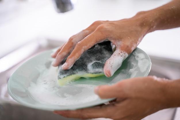 De vrouwelijke schoonmakende plaat die van het handgebaar spons gebruiken