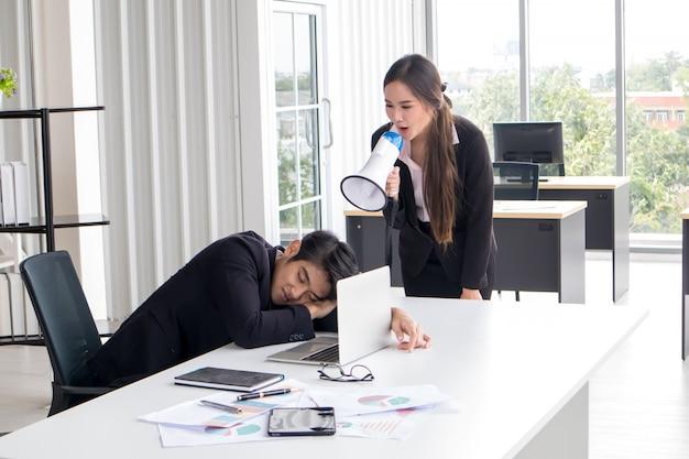 De vrouwelijke secretaresse houdt een megafoon vast om de baas wakker te maken die moe is.