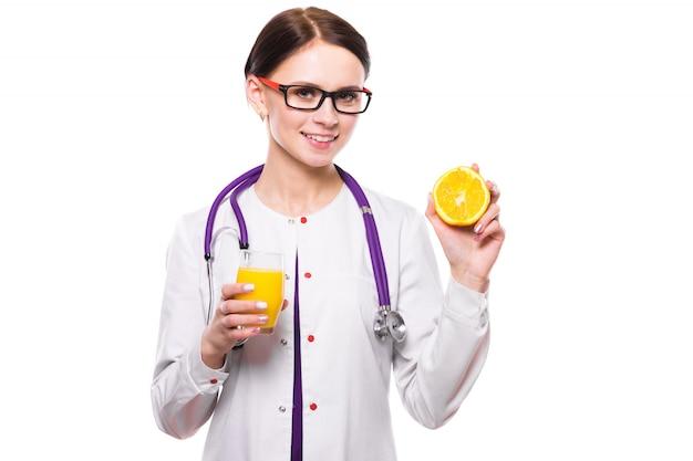De vrouwelijke sinaasappel van de voedingsdeskundigegreep in sectie en glas vers sap in haar handen op witte achtergrond