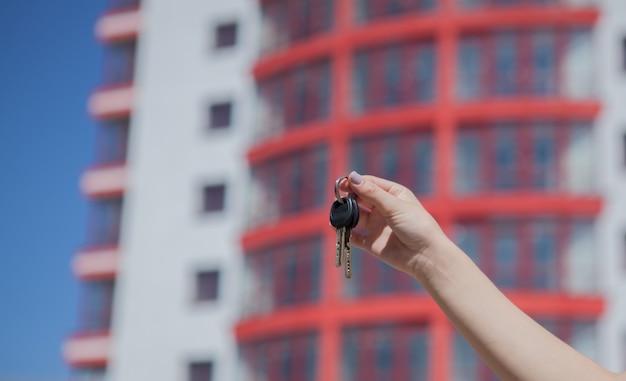 De vrouwelijke sleutels van de handholding op van van nieuw huis.