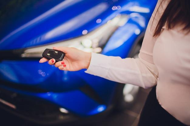 De vrouwelijke sleutels van de holdingsauto met auto