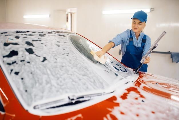 De vrouwelijke sproeier veegt de voorruit van de auto af