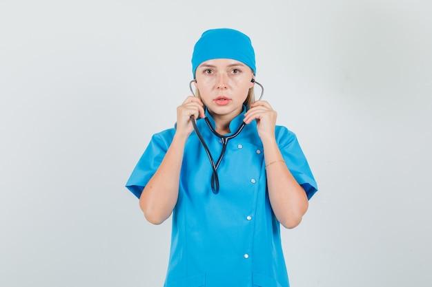 De vrouwelijke stethoscoop van de artsenholding in blauw uniform en op zoek ernstig