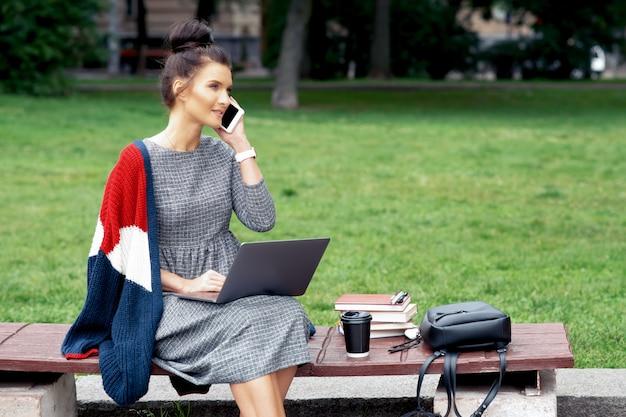 De vrouwelijke student met laptop spreekt door celtelefoon terwijl het zitten op de bank.