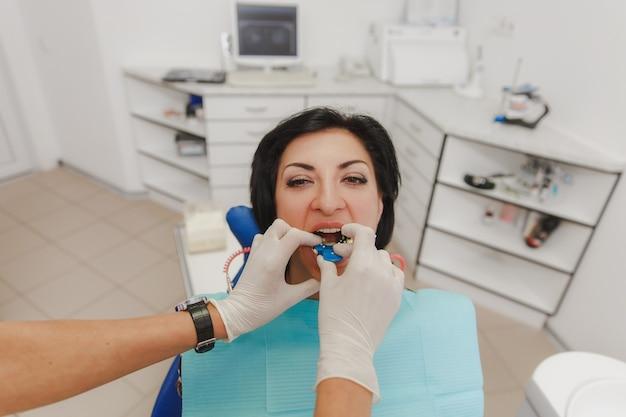 De vrouwelijke tandarts installeert in de mond van de patiënt een apparaat om een gegoten tand te maken