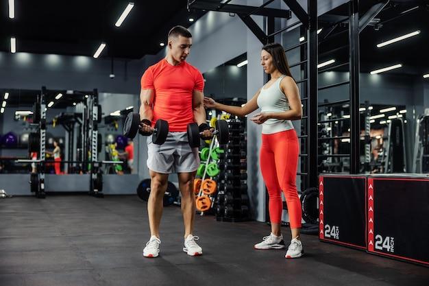 De vrouwelijke trainer laat de man met apparatuur zien en legt uit hoe de oefening correct moet worden uitgevoerd. ze bevinden zich in een grote moderne fitnessruimte met spiegels. sport, fitnesscoach