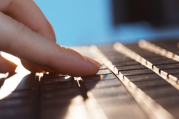 De vrouwelijke vingers op het laptop toetsenbord sluiten omhoog