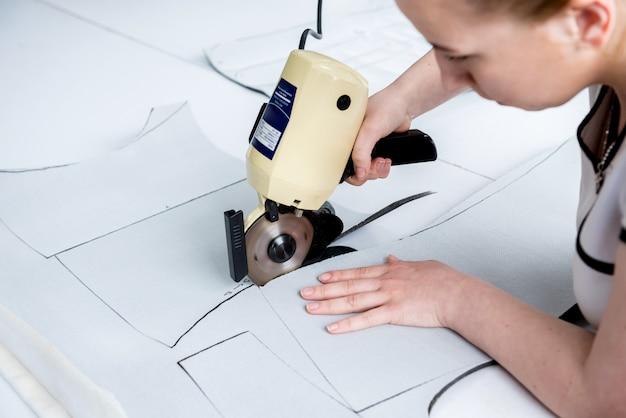De vrouwelijke werknemer gebruikt elektrische scherpe stoffenmachine. fabricage van de textielindustrie