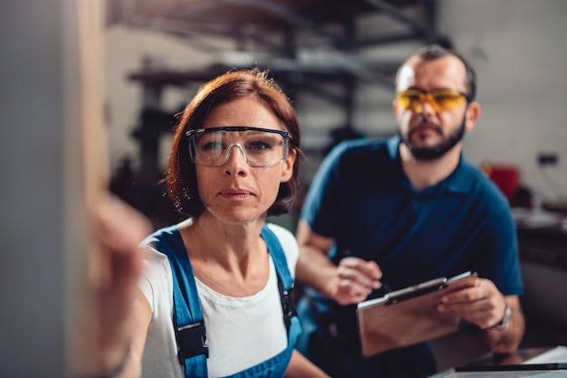 De vrouwelijke werknemer stelt machine in fabriek in werking