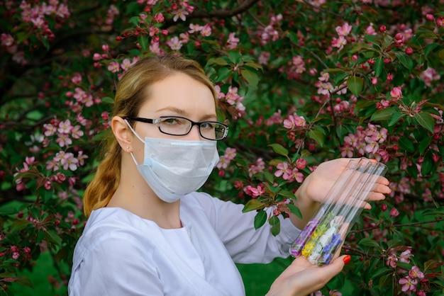 De vrouwelijke wetenschapper in medisch masker met reageerbuizen in haar handen bestudeert de eigenschappen van installaties in botanische tuin. het creëren van bloemengeuren, natuurlijke cosmetica, kruidengeneeskunde, aromatherapie, parfums.