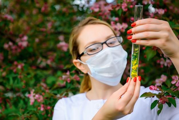 De vrouwelijke wetenschapper in medisch masker met reageerbuizen in haar handen bestudeert de eigenschappen van installaties in botanische tuin.