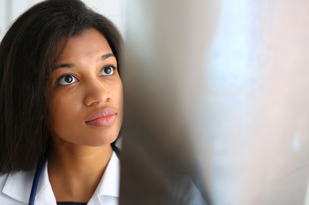 De vrouwelijke zwarte arts houdt in wapen en kijkt röntgenstraal