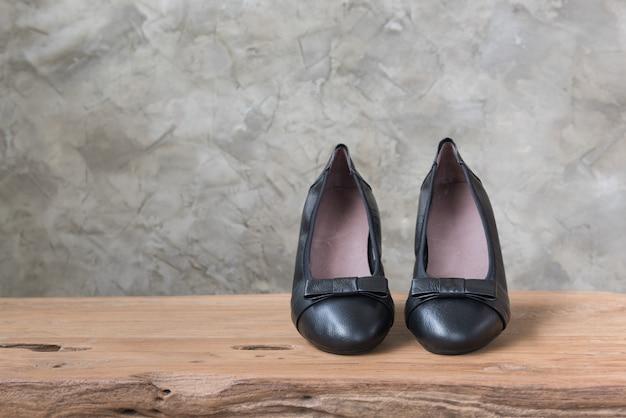 De vrouwelijke zwarte schoenen tonen op antieke houten lijst
