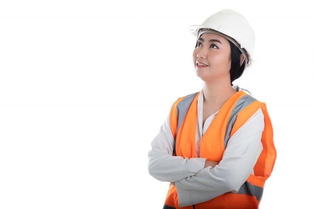 De vrouwen civiel-ingenieur die van portret mooie jonge azië vooruit en aan een witte muur denken denken, die bij de bouw de bouwconcept plannen