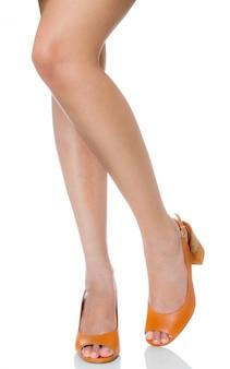 De vrouwen gekruiste benen stellen status dragend de manierschoenen van de leer stevige hoge die hiel met vooraanzichtprofiel op wit wordt geïsoleerd