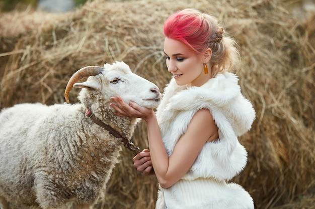 De vrouwen heldere rode make-up op gezicht koestert gehoornde schapen.