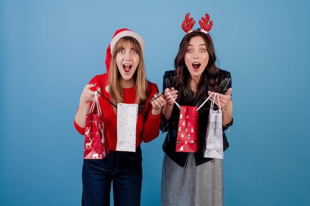 De vrouwen met stelt in kleurrijke het winkelen zakken voor die kerstmishoed en de winterkleren dragen over blauw worden geïsoleerd