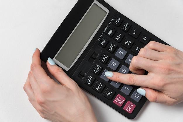De vrouwen overhandigen en calculator op een witte oppervlakte. budget planning concept