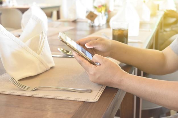De vrouwen overhandigen het gebruiken van telefoon op vaatwerk in restaurant.